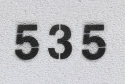 Black Number 535 on the white wall. Spray paint.