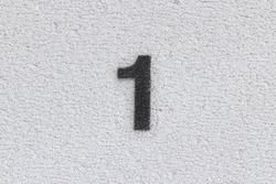 Black Number 1 on the white wall. Spray paint.
