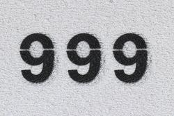 Black Number 999 on the white wall. Spray paint. Number nine hundred ninety nine.