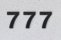 Black Number 777 on the white wall. Spray paint. Number seven hundred and seventy seven.