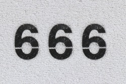 Black Number 666 on the white wall. Spray paint. Number six hundred sixty-six.