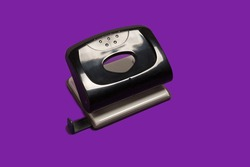 black office hole puncher on purple background. office accessories