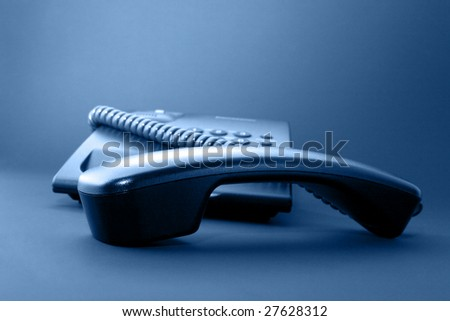 Black office phone and handset isolated on black background and blue toned