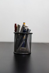 Black office pot with pencils and pens on a white background. Metal pen pot on black desk.