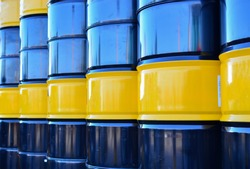 Black oil barrel. Petroleum drum containers. Gasoline barrels background. Crude mining concept and graph of falling oil prices on the trading exchange. Crude oil pump jack at oilfield.