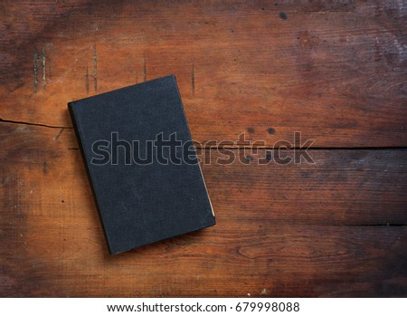 Black old closed book on wooden table. Top view, copy space