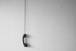 black old handset with a wire hang against wallpaper texture. black plastic telephone hanging by the cord.Retro Phone Cord - Vintage Telephone Handset Receiver hanging by the Cord down