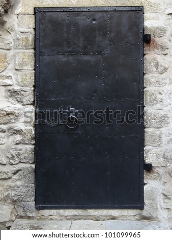 Black old metal door texture with iron handle and brick wall around