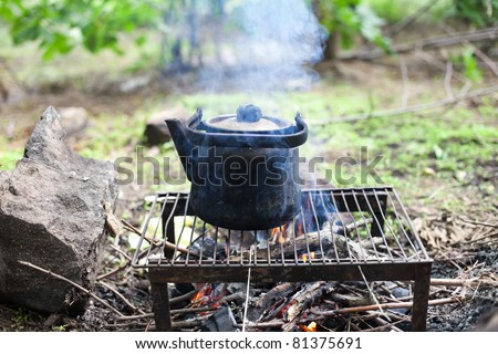black old smoked teapot on the campfire on picnic in wood in the summer - stock photo
