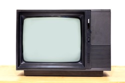 Black old television on wooden table with white wall background.