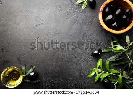 Black olives and olive oil in wooden bowls on black background. Top view with copy space for text. Stock photo ©