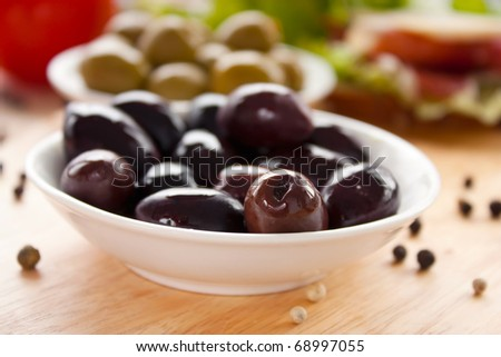 Black olives in a bowl on  a wooden board.Shallow depth of field.