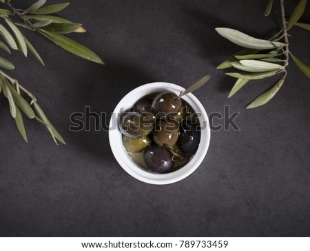 Black olives in dark background with olive tree leaves. #789733459