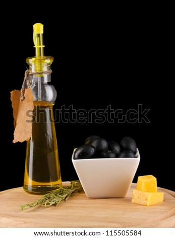Black olives in white bowl with rosemary,olive oil and cheese on board isolated on black