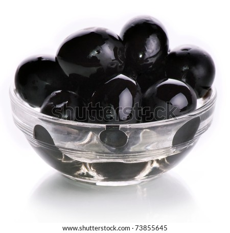 Black olives watered with oil in a glass glass on a white background
