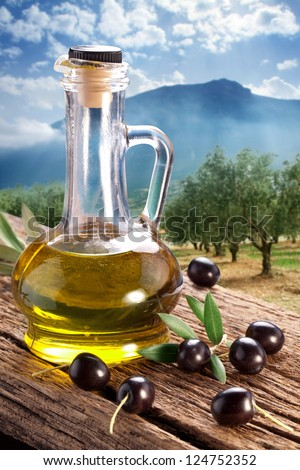 Black olives with bottle of oil on a wooden table on a background of olive garden.