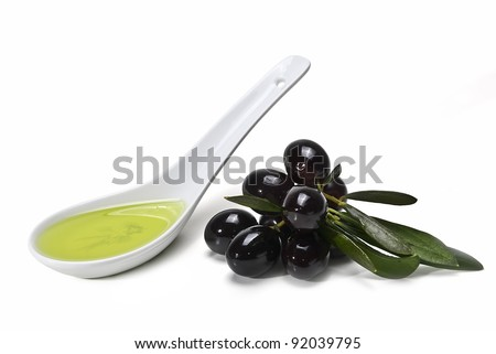 Black olives with leaves and a spoonful of olive oil isolated over a white background.