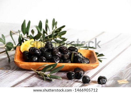 Black olives with leaves and lemon. Black olives at wooden bowl isolated on white wooden background. Stok fotoğraf ©