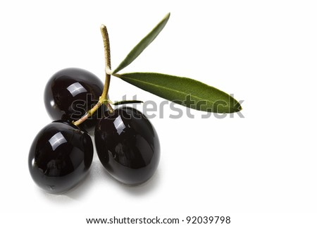 Black olives with leaves isolated over a white background.