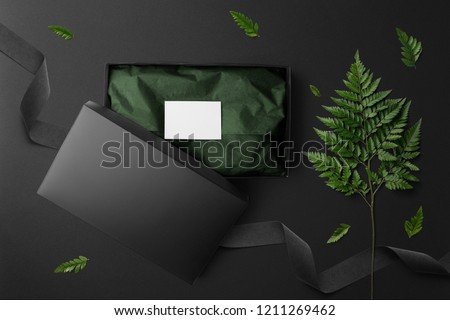 Black open box mockup and stationery set, top view, with floral elements, flowers and blank copy space on black background.