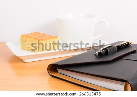 black organizer with black pen coffee and cake ,coffee break on wooden table