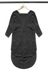 Black oversized tunic hanging on wooden clothes rack isolated over white
