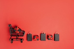 black paper bags and gift boxes with shopping cart on red background, copy space. black friday concept