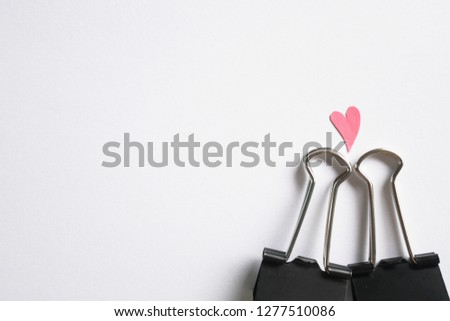 Black paper clip with no face and pink heart above head #1277510086