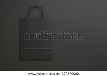 black paper shopping bag on black background with handles. 3d render