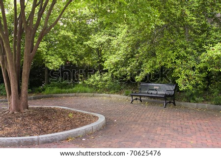 Black park bench on red brick