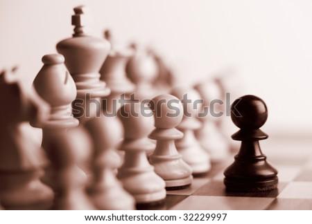 Black pawn and white chess pieces sepia tone