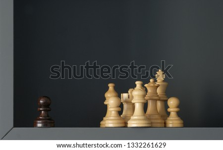 Black pawn standing outside a group of white chess pieces #1332261629