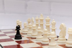 Black pawn stands in front of the exposed white chessmen. Concept of chess strategy, opposition, courage, unequal forces. Selective focus, blurred background