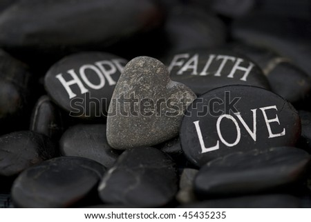 stock photo : black pebble with engraved message love, faith, hope and stone