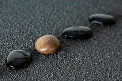 Black pebbles on black sand background with brown pebble. Concept of diversity or singularity