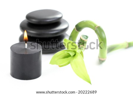 black pebbles with green bamboo and candle on white
