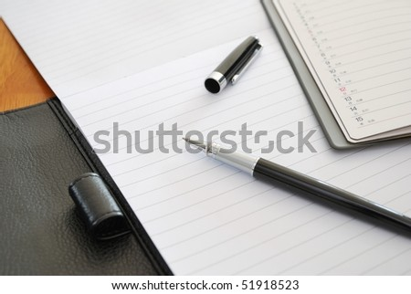 Black pen on blank writing pad or planner signifying concepts such as office and business, and work related objects