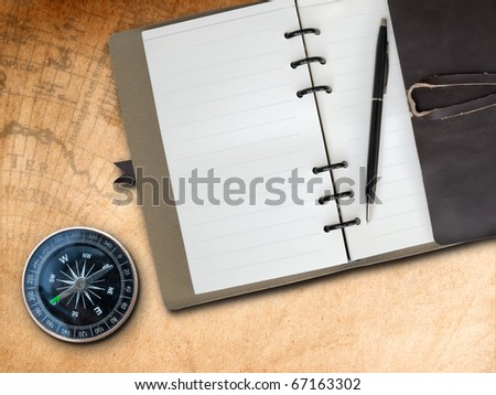 Black pen with Brown Leather cover note book and Compass on old map background