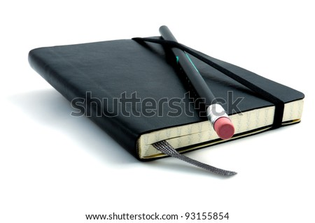 Black pen with pink rubber on black leather moleskin notebook isolated on white.