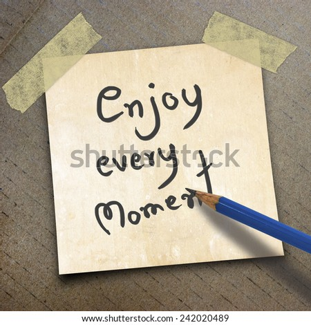 black pencil and text enjoy every moment on shortnote paper on the packing paper box texture background