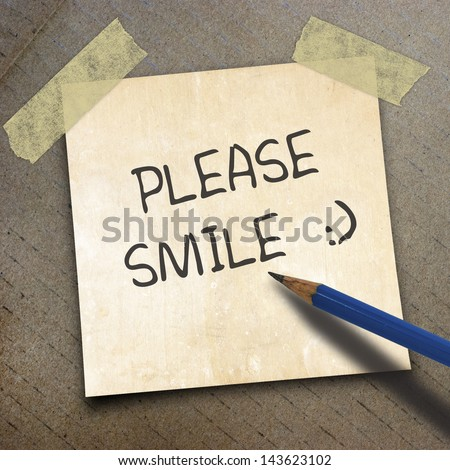 black pencil and text please smile   on shortnote paper on the packing paper box texture background