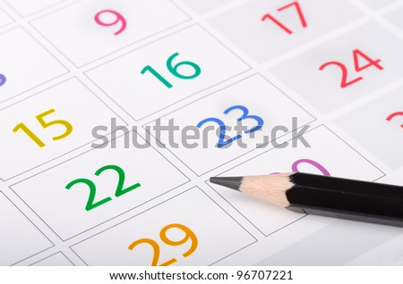 Black pencil on calendar page with colorful dates