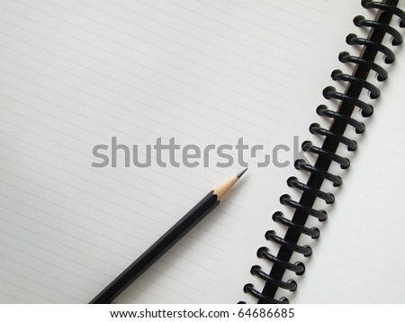 Black pencil on open white paper note book top view