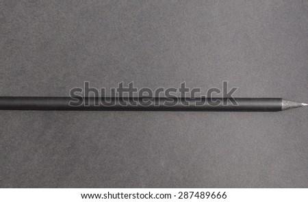Black pencil over a black paper background