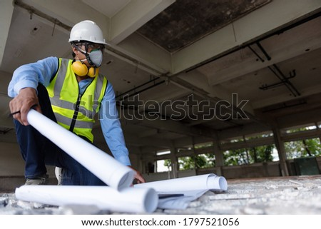Black People Construction Worker wearing face mask and safety helmet while looking to an area follow drawing on construction site. Civil Engineering or Surveyor checking in the demolished building.
