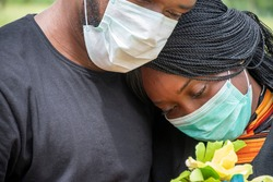 black people mourning lost ones to coronavirus, wearing face masks, showing support for each other