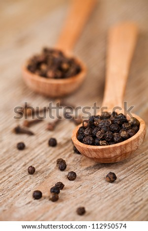 black pepper and cloves in wooden spoons on rustic wooden background