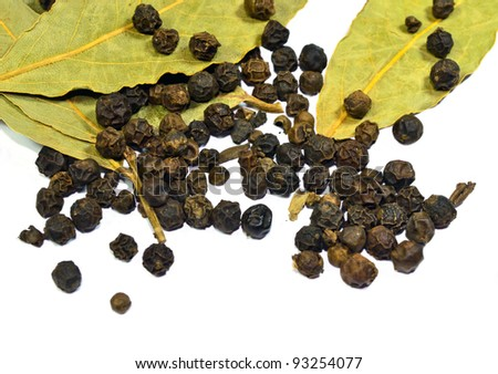 Black pepper and dry bay leaves isolated on white