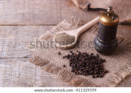 Black pepper corns and Black pepper Powder on wooden background #411329599