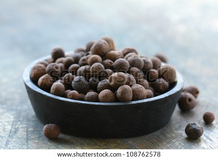 black pepper in a wooden bowl - stock photo